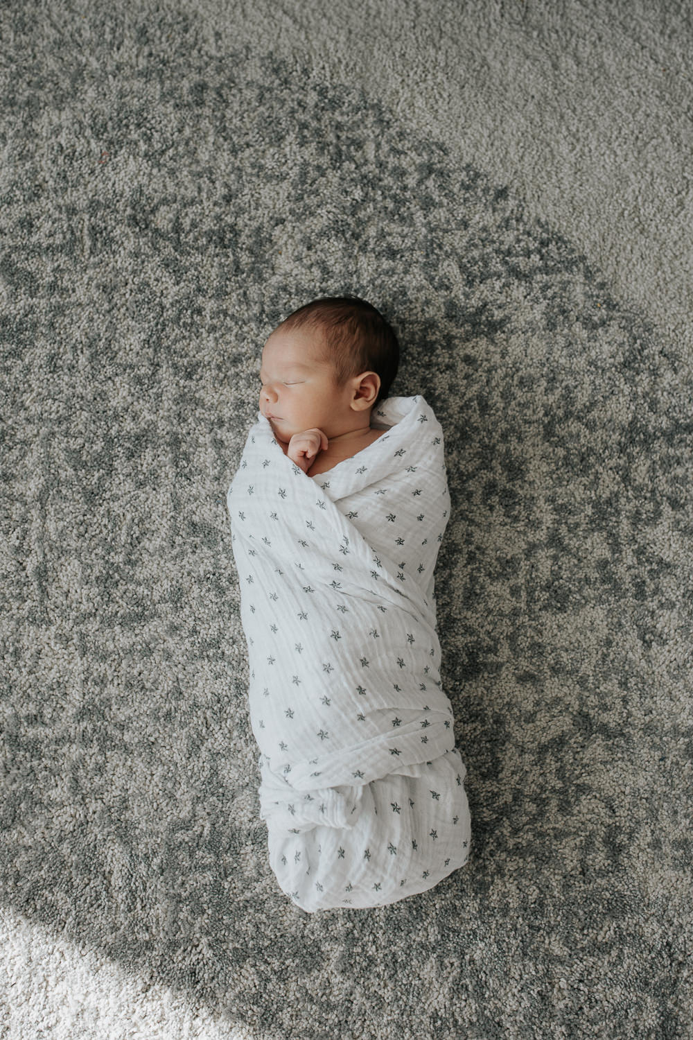 2 week old baby boy with dark hair and olive skin wrapped in swaddle with star on it, sleeping with hand near face -Stouffville Lifestyle Photos