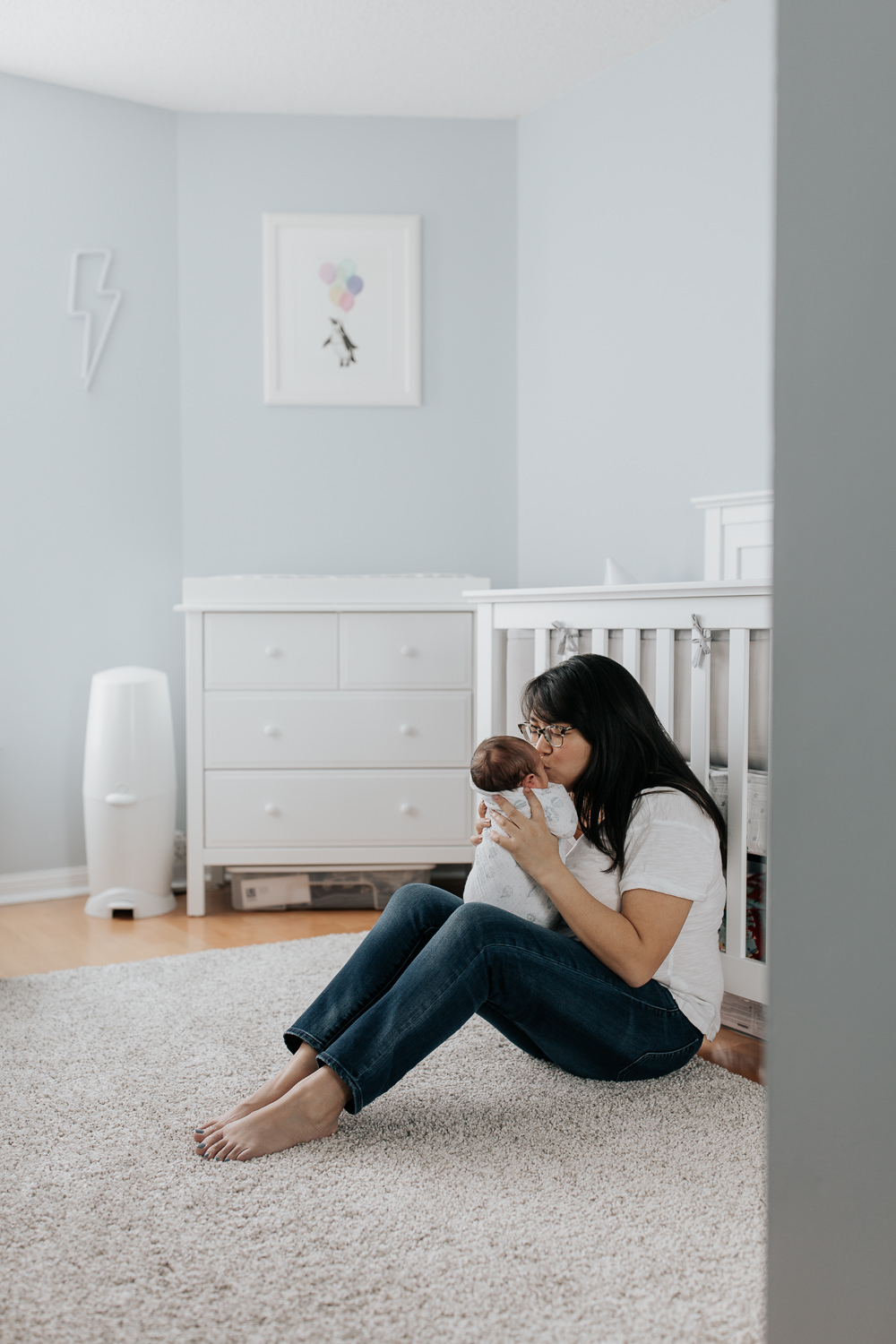new mother with long dark hair wearing glasses sitting in front of nursery crib holding 2 week old baby boy in her arms, kissing son on forehead -York Region Lifestyle Photography