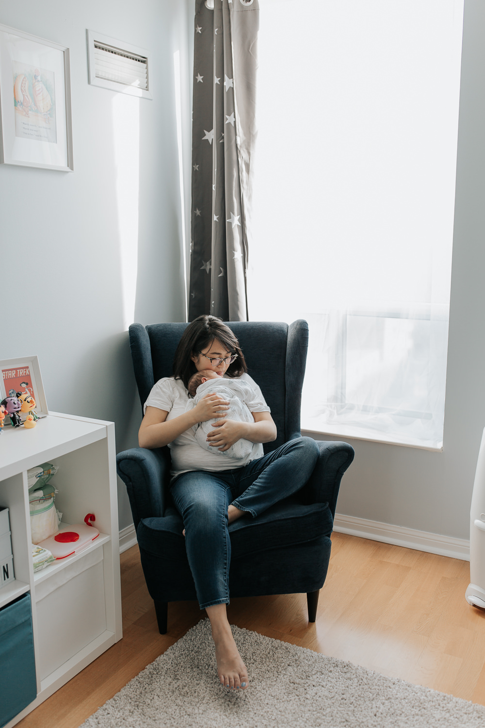 new mother with long dark hair wearing glasses  sitting in blue nursery chair with 2 week old baby boy in swaddle asleep on her chest, mom's cheek resting against top of son's head - York Region In-Home Photos