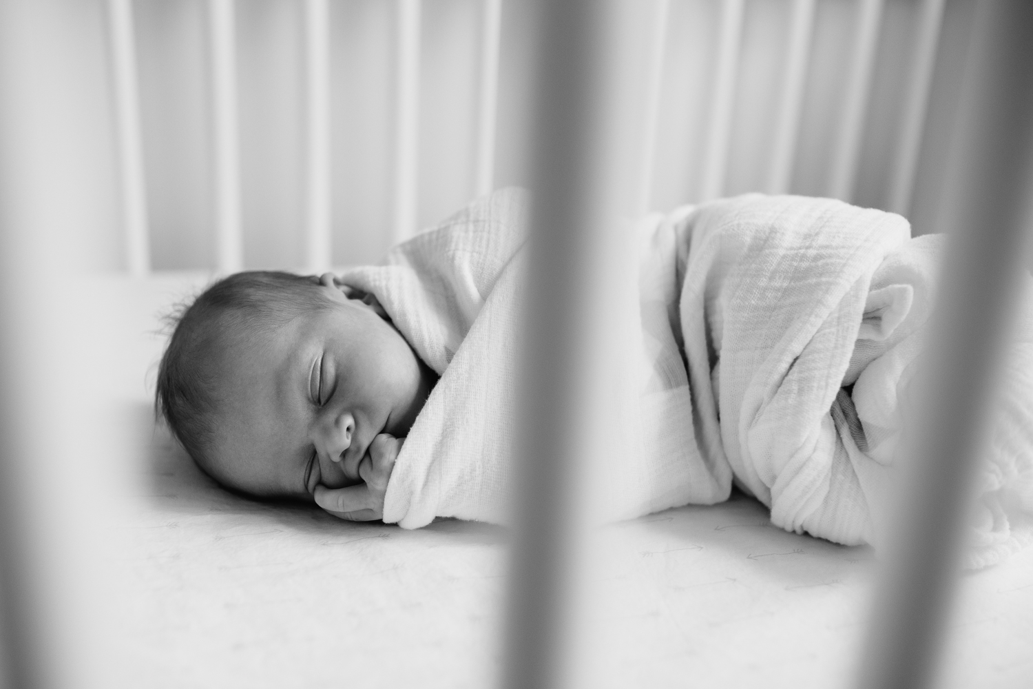 2 week old baby boy in white swaddle with grey stars, lying asleep in white crib with wood trim in nursery, chewing on fingers - Barrie In-Home Photos