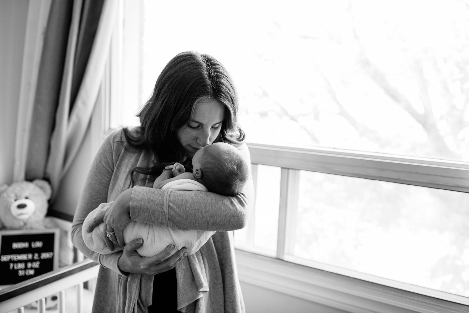 new mom with long red hair standing in neutral nursery holding and snugging 2 week old baby boy wrapped in white swaddle, mother kissing son on head - York Region In-Home Photos