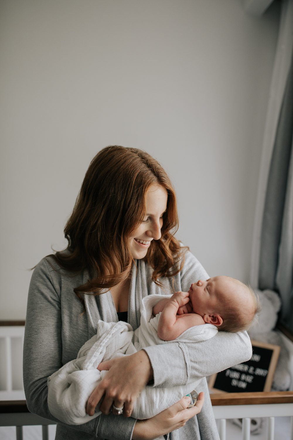 new mom with long red hair standing in neutral nursery holding and snugging 2 week old baby boy wrapped in white swaddle, mother smiling at son who has hands tucked under his chin -Stouffville Lifestyle Photos