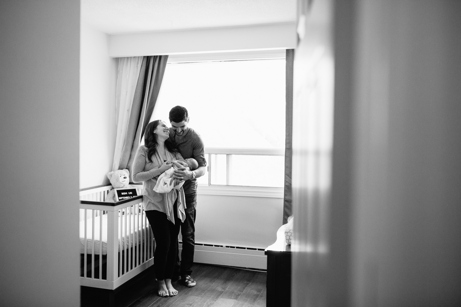 new parents standing in front of crib in neutral nursery, mother holding 2 week old baby boy wrapped in white swaddle, father with arms around wife, hand on son, laughing - Barrie Lifestyle Photos