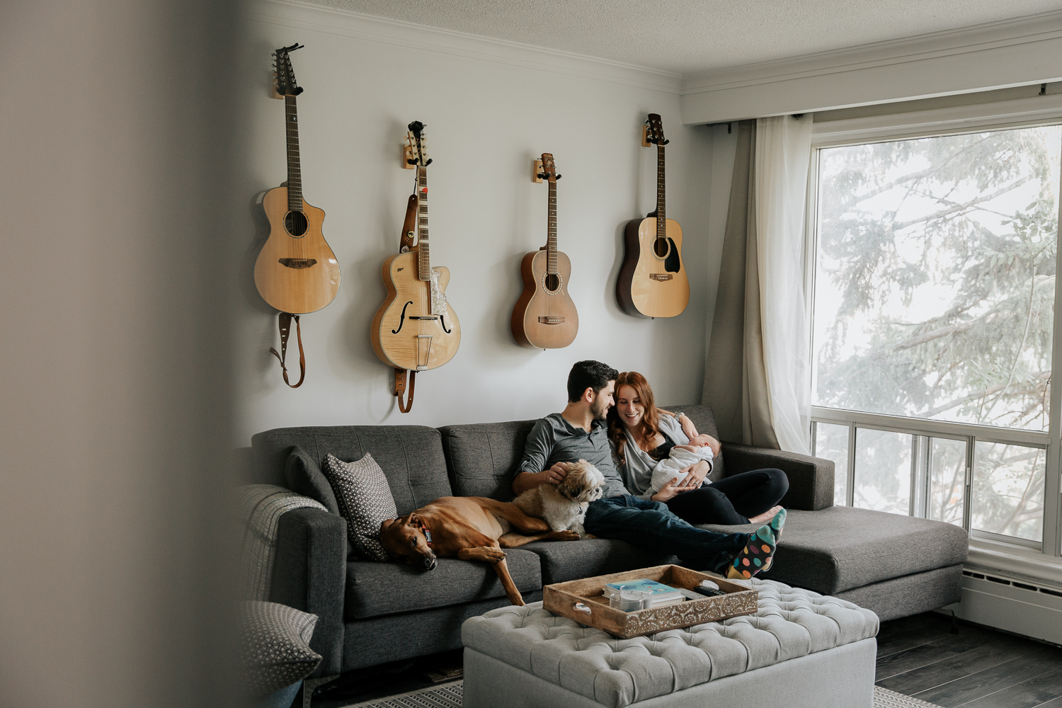 new parents sitting on living room couch, mom holding 2 week old baby boy, large and small dog lying on couch next to father, mother smiling at them - Markham In-HomePhotography