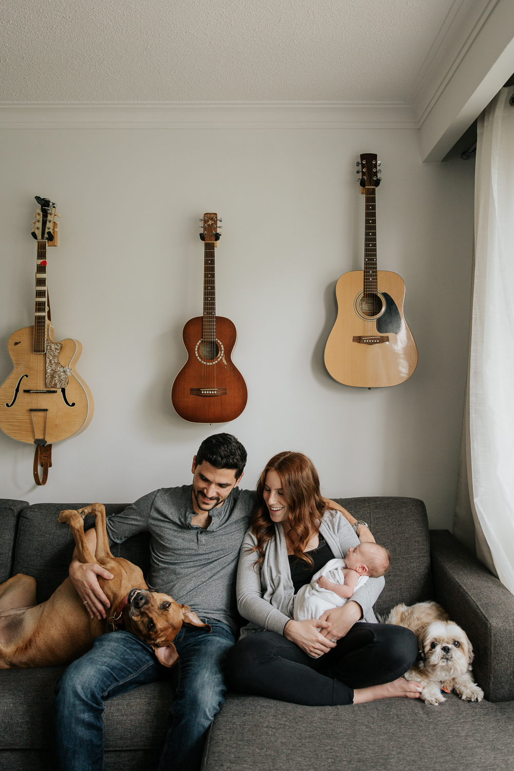 new parents sitting on living room couch, mom holding 2 week old baby boy, large brown dog lying with head in dad's lap legs in air, small dog sitting beside mother, looking at camera -Newmarket In-Home Photos