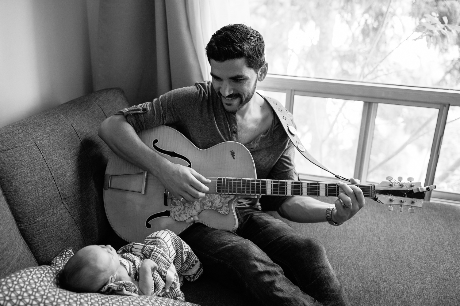 new dad sitting on living room couch playing guitar and singing to 2 week old baby boy lying against cushions - York Region LifestylePhotography