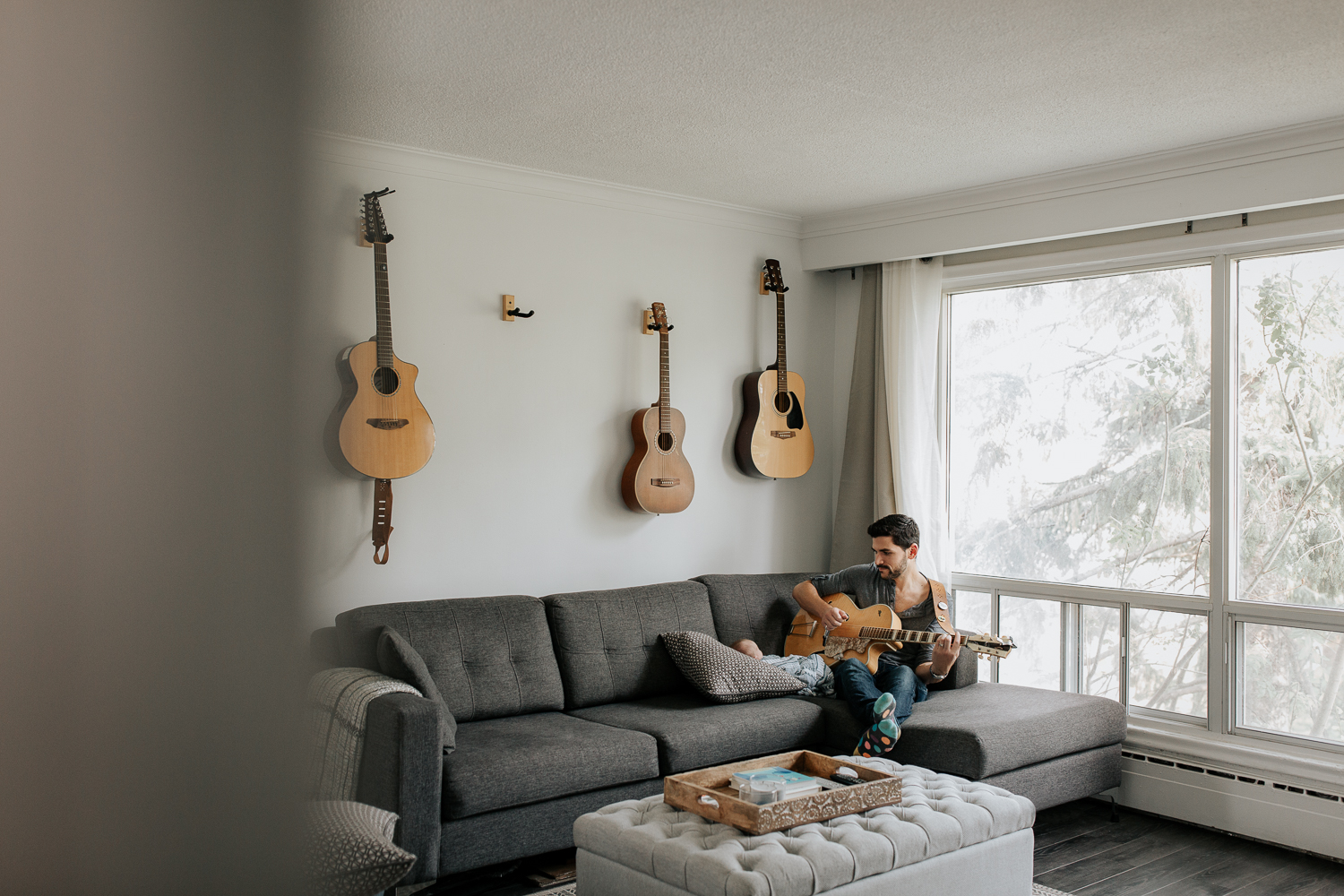 new dad sitting on living room couch playing guitar and singing to 2 week old baby boy lying against cushions - Newmarket In-HomePhotography