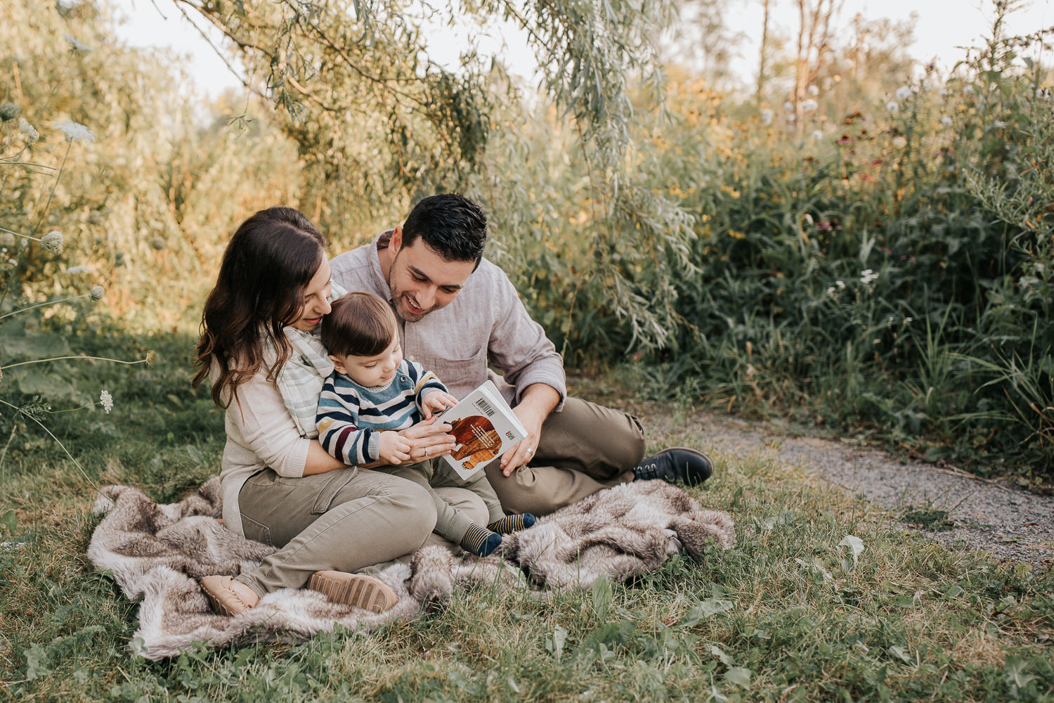 family of 3 sitting on fur blanket under willow tree at sunset, 1 year old baby boy sitting on mom's lap reading story, dad next to them smiling down at son - Newmarket Lifestyle Photography