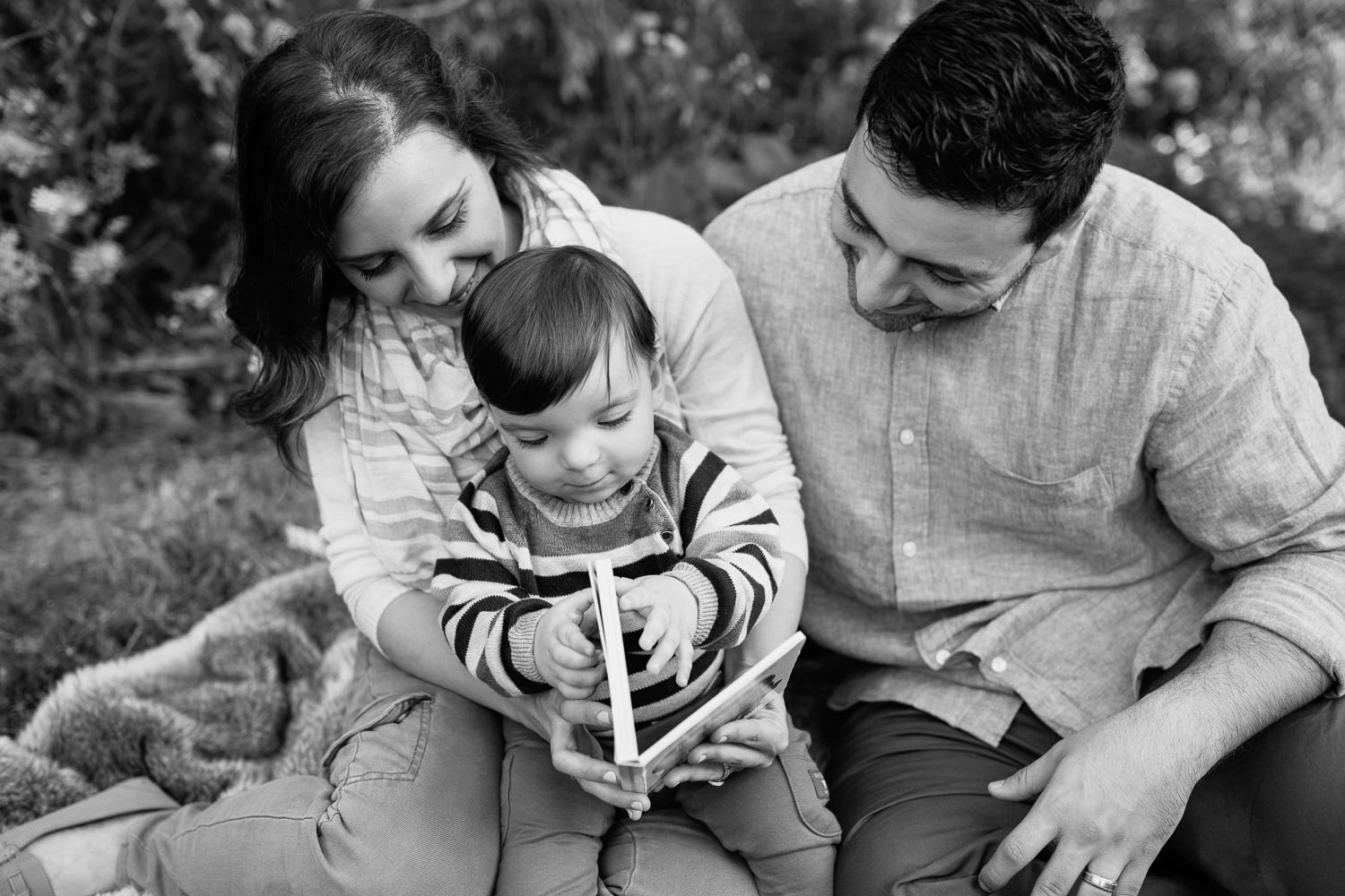 Markham Lifestyle Photographyfamily of 3 sitting on fur blanket under willow tree at sunset, 1 year old baby boy sitting on mom's lap reading story, dad next to them smiling down at son -
