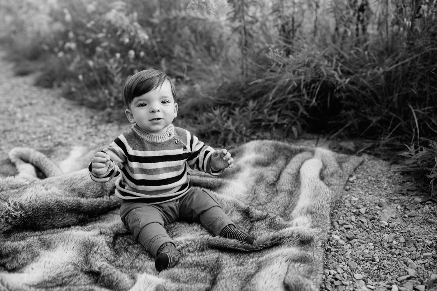 1 year old boy with dark hair and eyes wearing striped sweater sitting on blanket in outdoor path looking at camera - York Region Golden Hour Photography