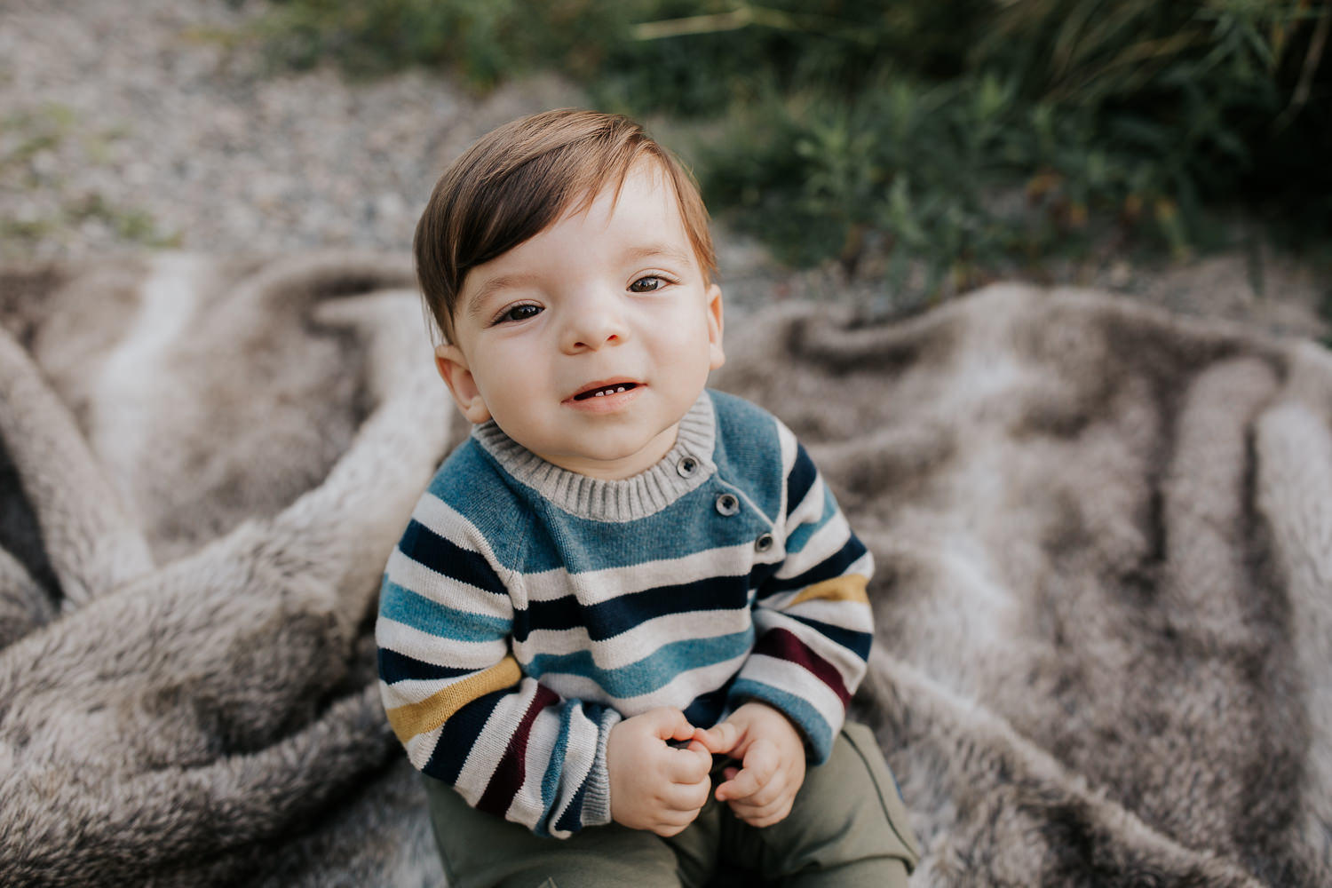 1 year old boy with brown hair and eyes wearing striped sweater sitting on blanket in outdoor path looking up at camera - Newmarket Golden Hour Photos