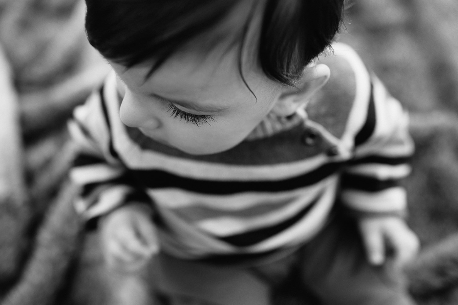 1 year old boy with dark hair and eyes wearing striped sweater sitting on blanket in outdoor path, close up of eyelashes - Stouffville Golden Hour Photos