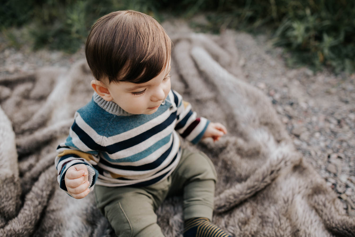 1 year old boy with brown hair and eyes wearing striped sweater sitting on blanket in outdoor path down - Markham Golden Hour Photos