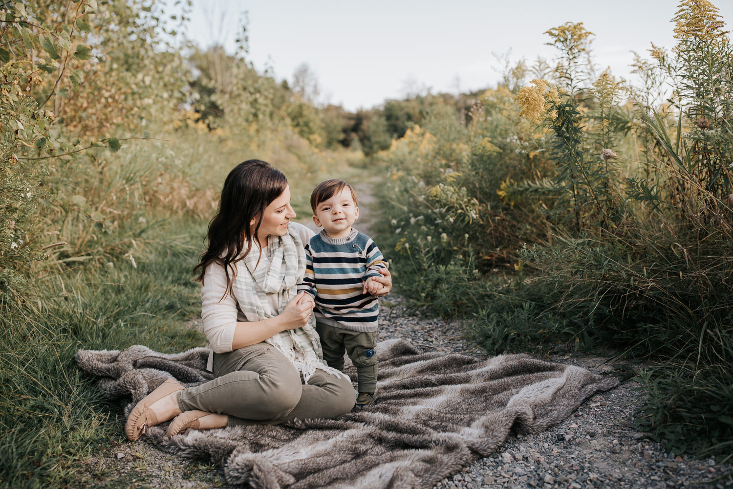 mother sitting on fur blanket on outdoor grassy path, 1 year old baby boy standing next to her, mom smiling at son, boy smiling at camera - Barrie Golden Hour Photography
