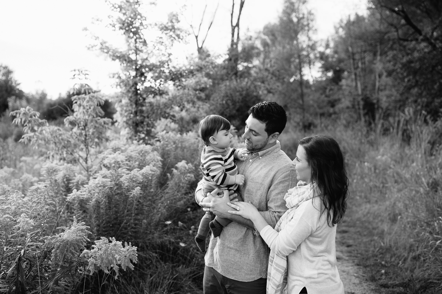 family of 3 standing on path in grassy field, dad holding 1 year old baby boy, mom standing behind husband, hand on his arm, looking at son - GTA Golden Hour Photos