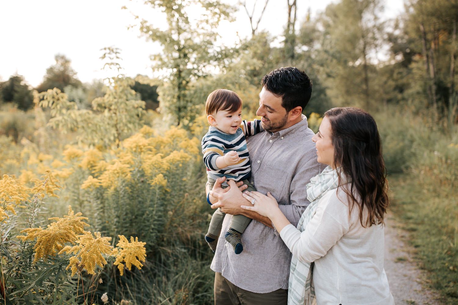 family of 3 standing on path in golden field, dad holding 1 year old baby boy, mom standing behind husband, hand on his arm, looking at son - Stouffville Lifestyle Photos