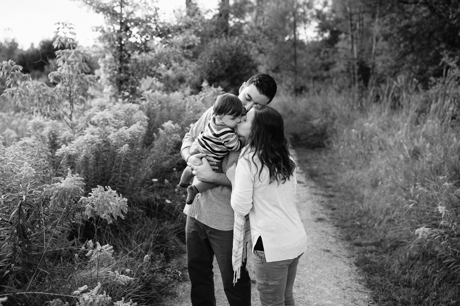 family of 3 standing on path in grassy field, dad holding 1 year old baby boy, mom standing next to husband, leaning over to kiss son - Markham Lifestyle Photos