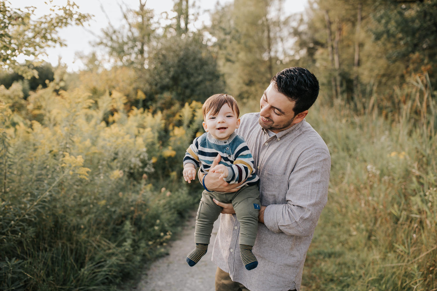dad standing in golden field holding 1 year old baby boy, son smiling at camera, father smiling at him - York Region Lifestyle Photos