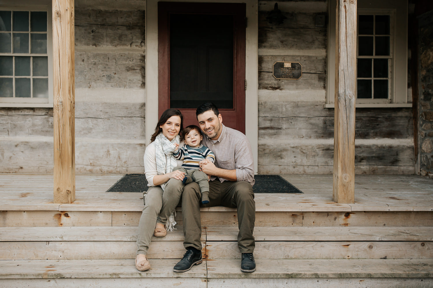 family of 3 sitting on front porch steps of historic log cabin, son on dad's lap, mom next to them, smiling at camera - Stouffville OutdoorPhotography
