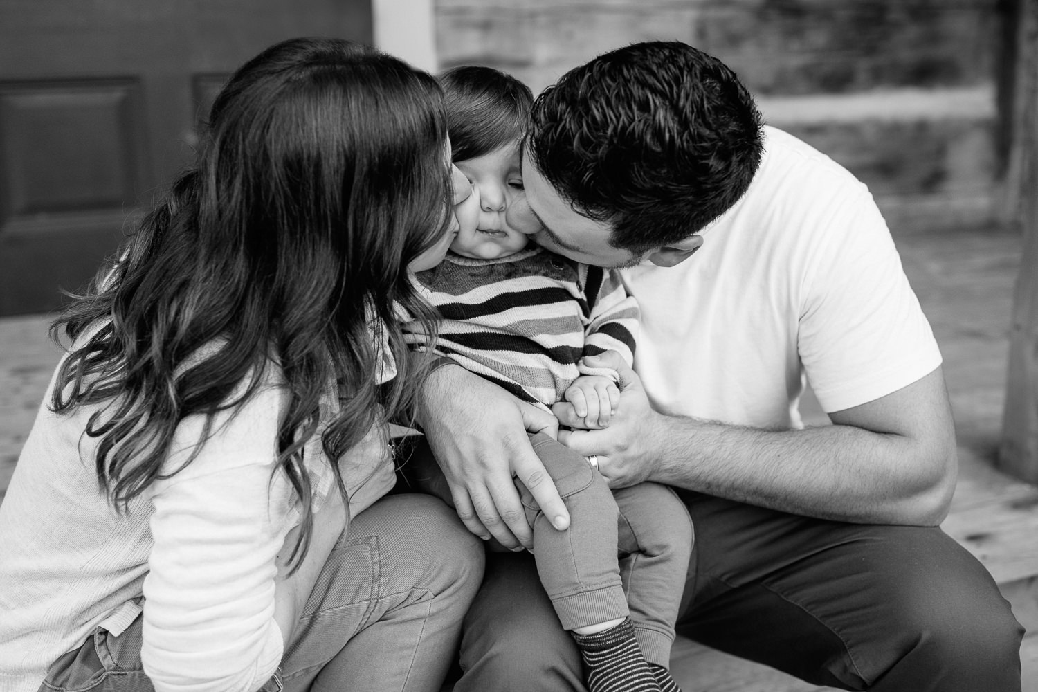 family of 3 sitting on front porch steps of historic log cabin, son between mom and dad, parents kissing child on cheeks - York Region Outdoor Photography