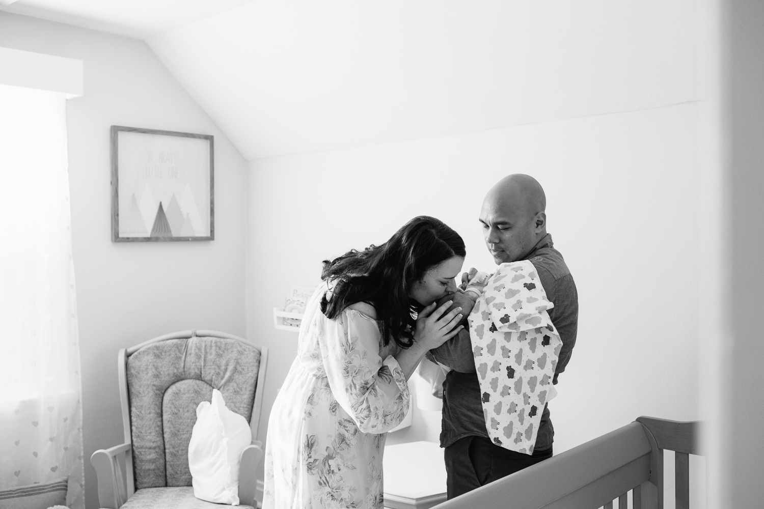 new parents standing in nursery, dad feeding 3 week old baby boy a bottle as mom stands next to them, hand on son's head, kissing him - Stouffville Lifestyle Photography