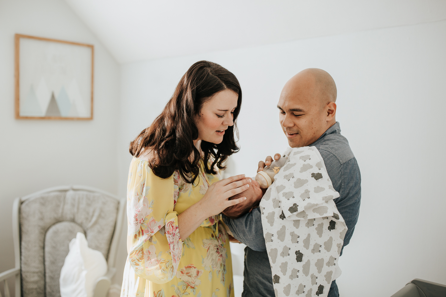 new parents standing in nursery, dad feeding 3 week old baby boy a bottle as mom stands next to them, hand on son's head - Newmarket Lifestyle Photography
