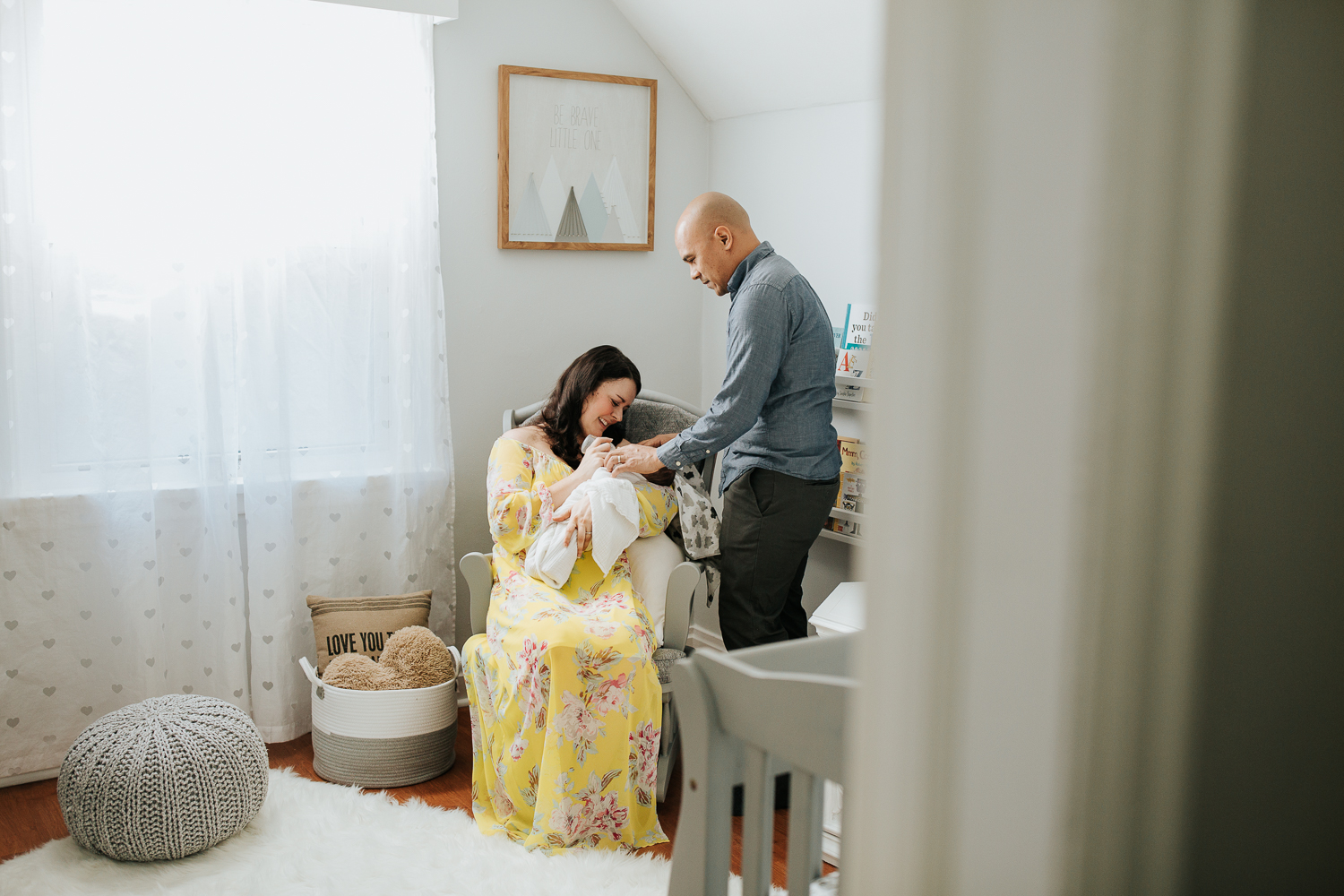 new mom in yellow dress sitting in nursery rocker feeding 3 week old baby boy his bottle, father standing next to chair holding son's hand - GTA Lifestyle Photography