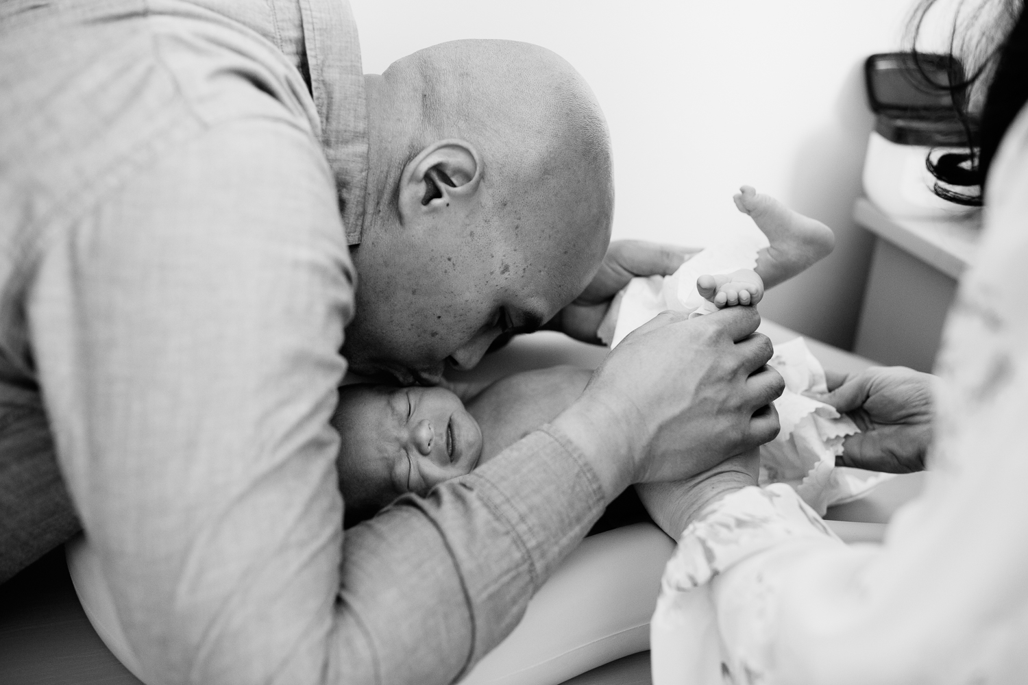 new dad kissing 3 week old baby boy's cheek as he cries getting diaper changed by mom - Barrie In-Home Photography