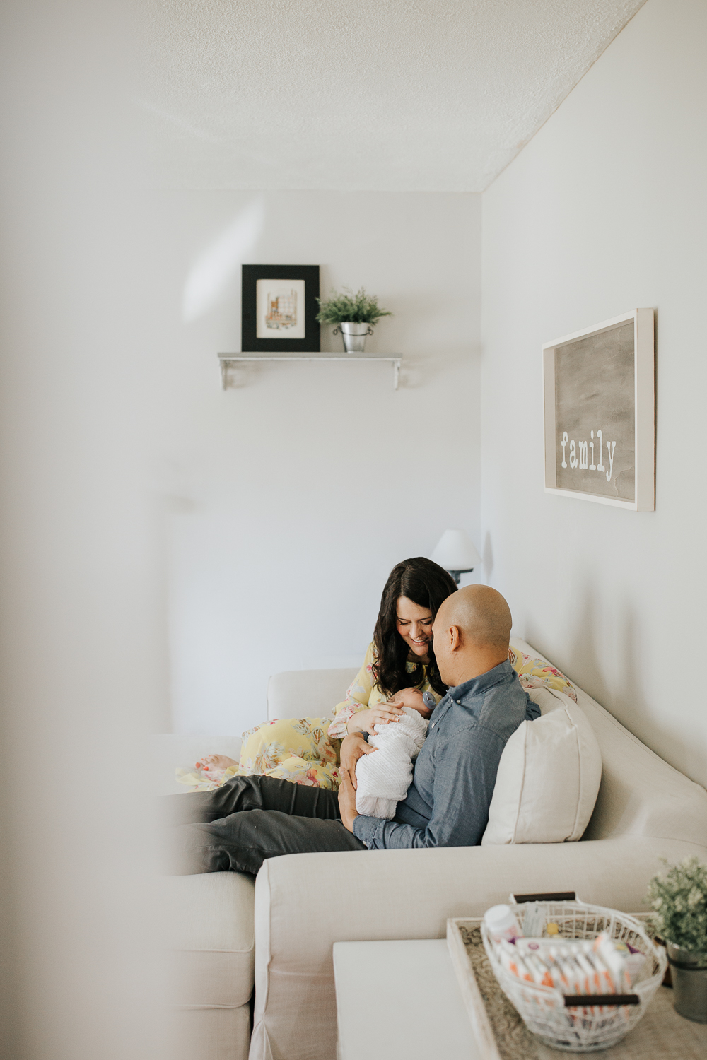 new parents sitting on couch, 3 week old baby boy in father's arms, mother smiling at son - Barrie Lifestyle Photography