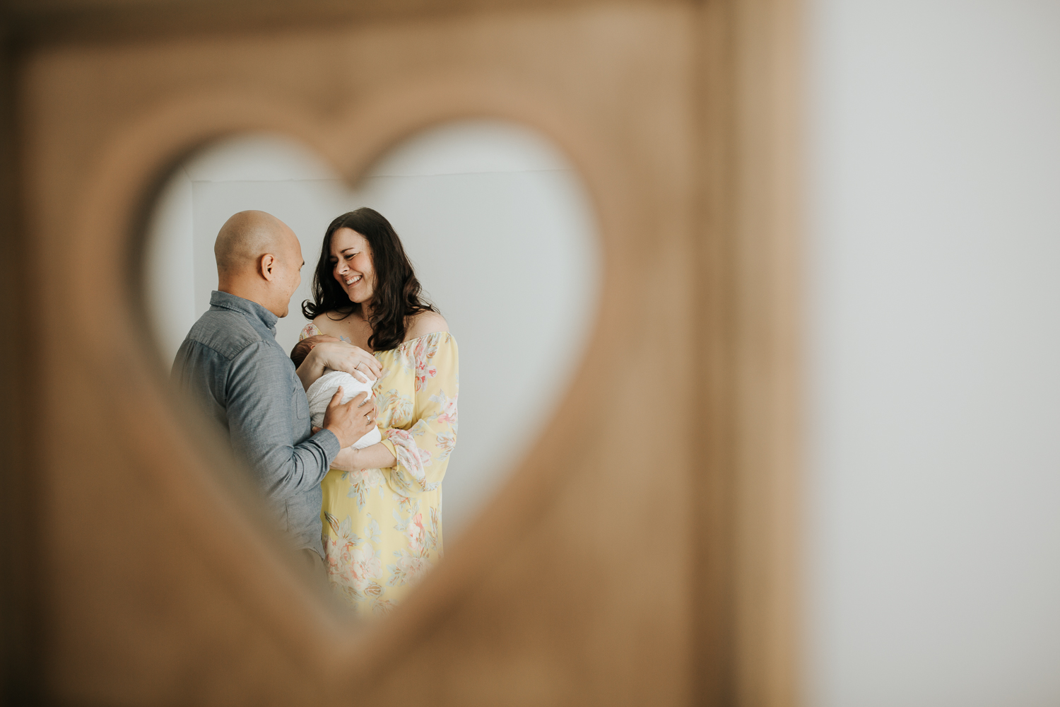new parents framed in heart mirror, mother holding sleeping 3 week old baby boy to her chest, smiling at husband, dad's hand on son - GTA LifestylePhotos