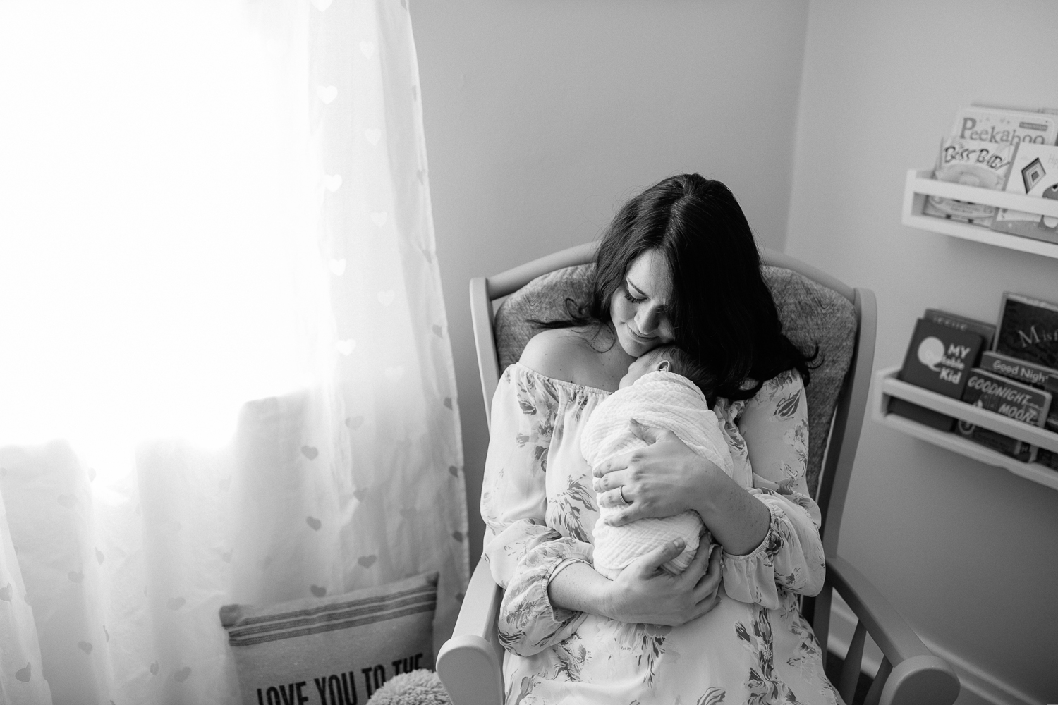 new mother sitting in nursery rocker snuggling 3 week old baby boy on her chest, mom's chin resting on son's head - Markham Lifestyle Photography