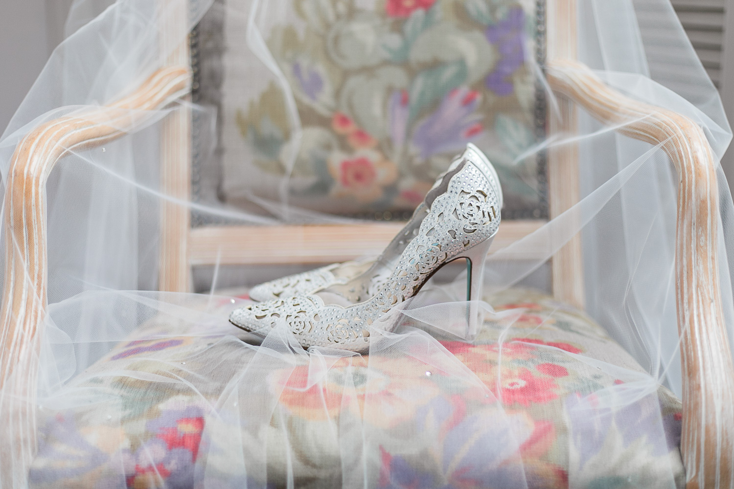 Wedding veil on a chair with wedding shoes