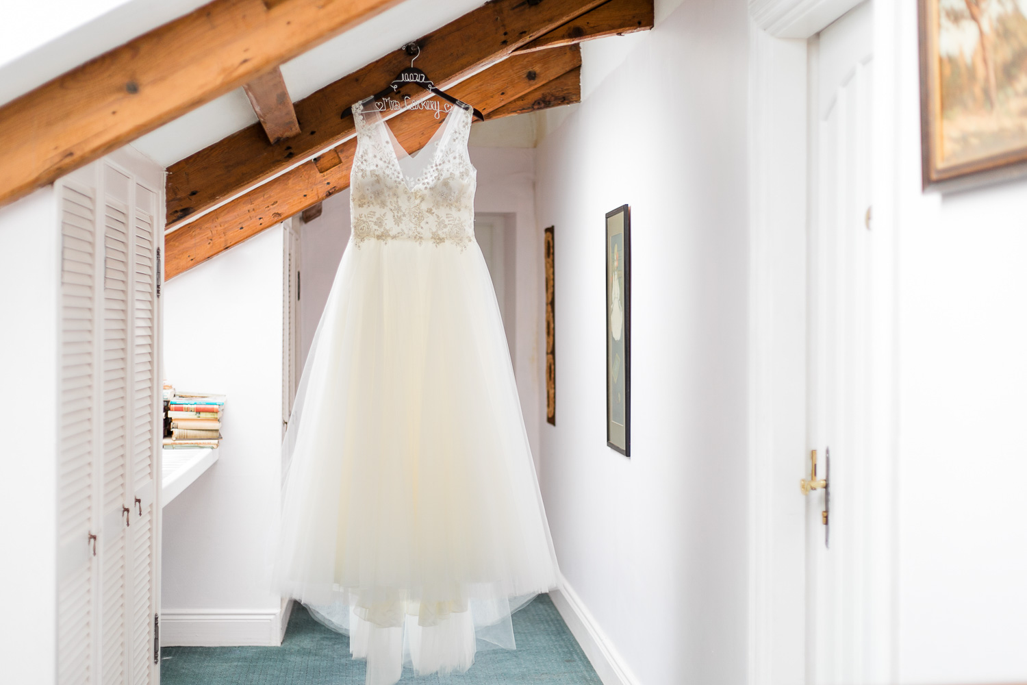 Wedding dress hanging of wooden beams in the converted attic of a castle