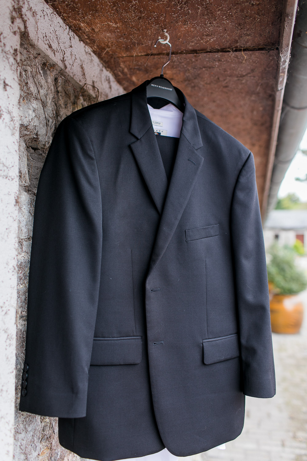 Groom's suit hanging outside on wooden beams
