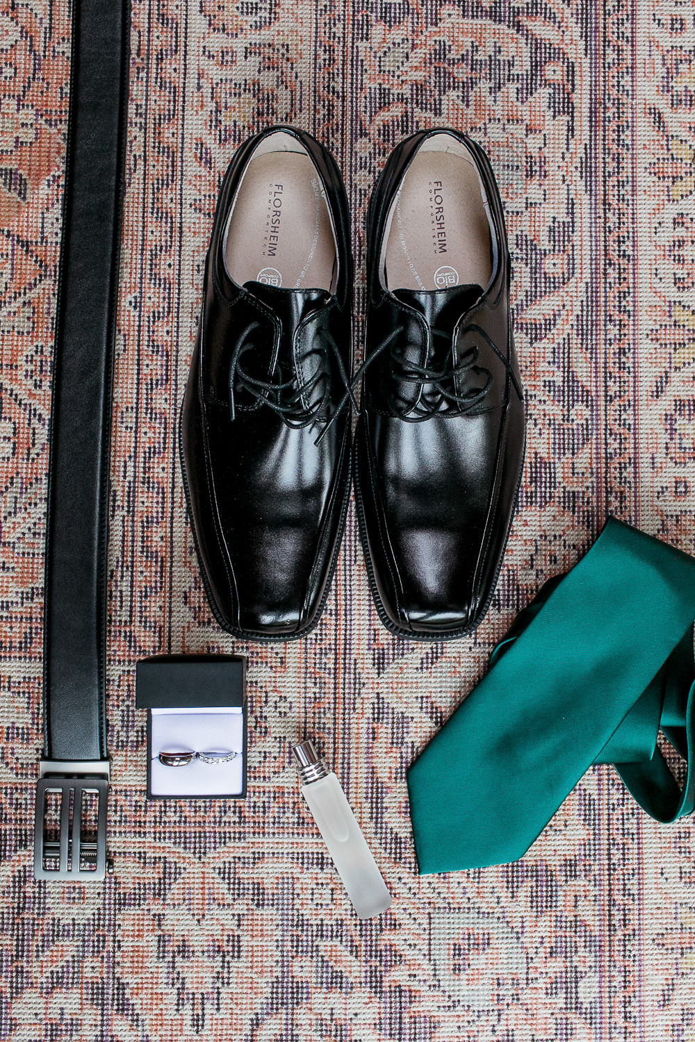 Details of groom's shoes, green tie, belt, rings on a one hundred year old vintage rug