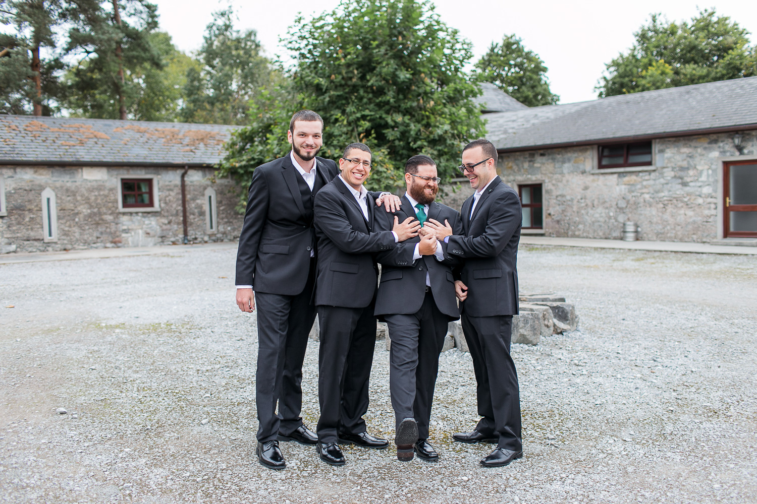 Groomsmen surrounding the groom standing in the courtyard of the refurbished stables