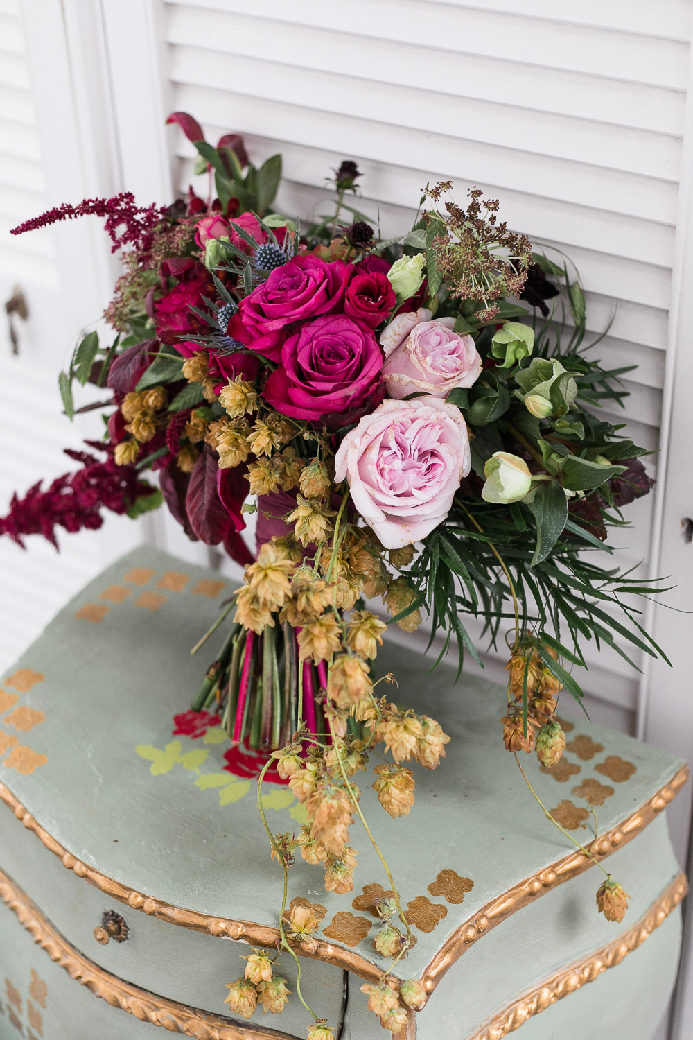 Wedding flowers with roses and hanging details on a vintage cabinet