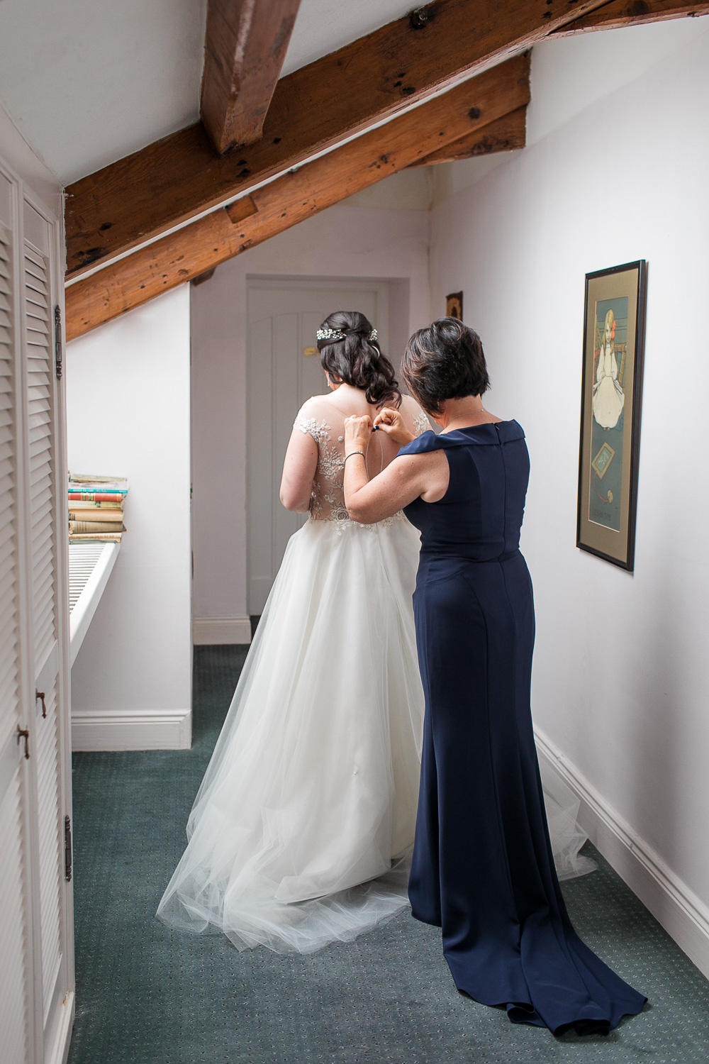 The mother of the bride helping to get into the wedding dress on the morning of the wedding day