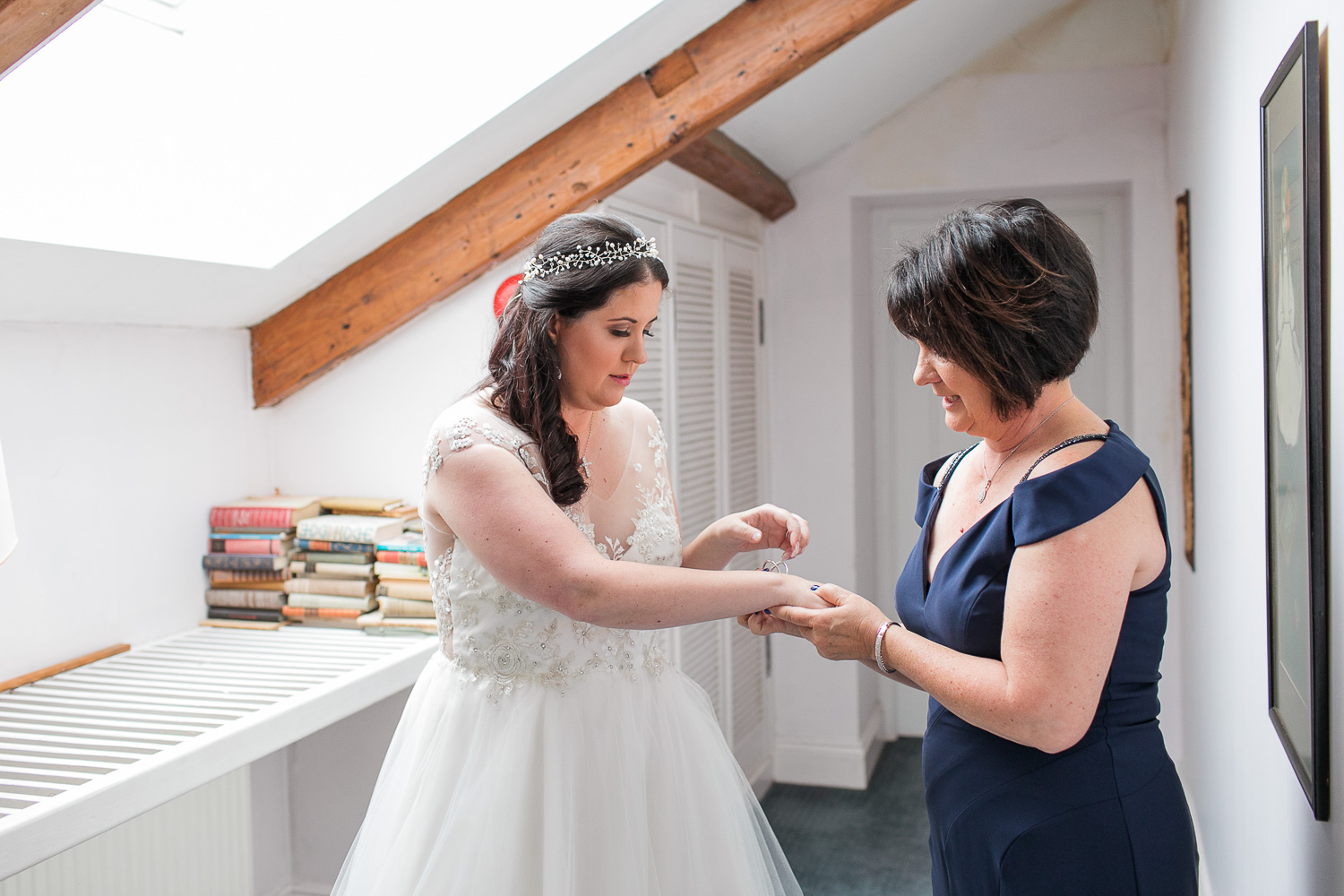 Mom putting on a bracelet on her daughter before her wedding ceremony