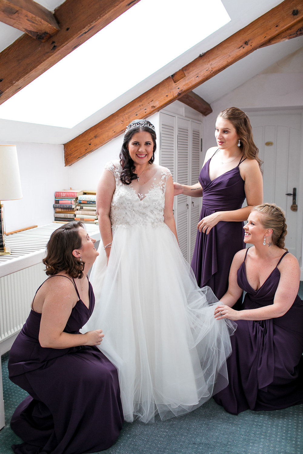Bridesmaids helping the bride with her wedding dress on the day of her wedding