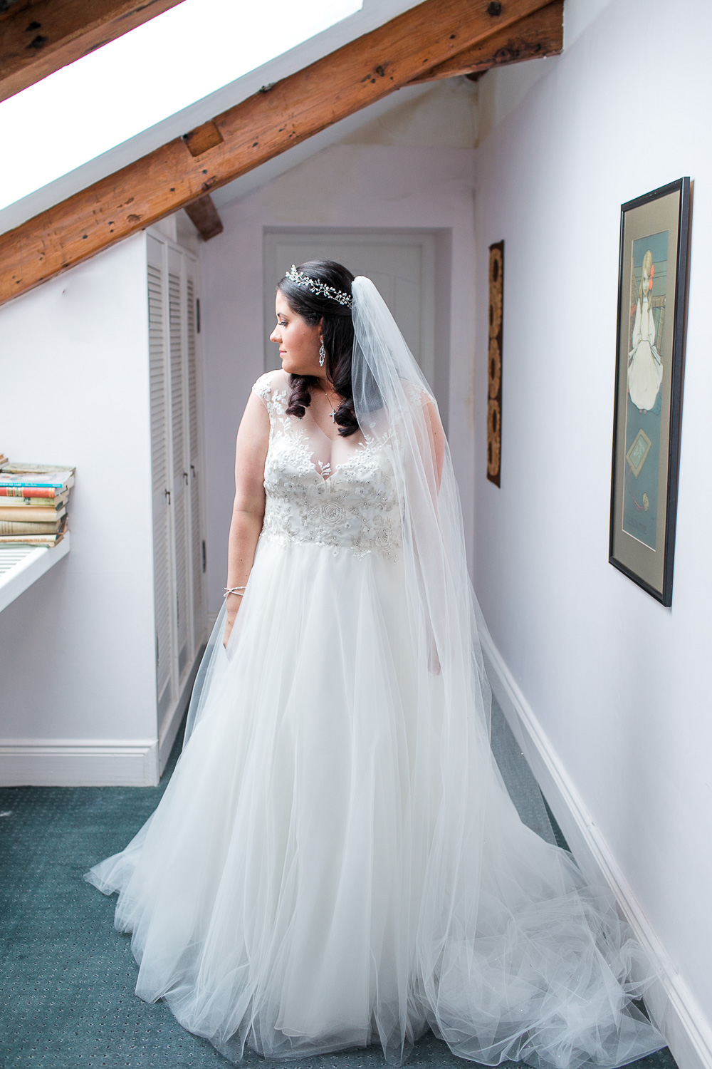 Bride standing lit by window light underneath the wooden beams