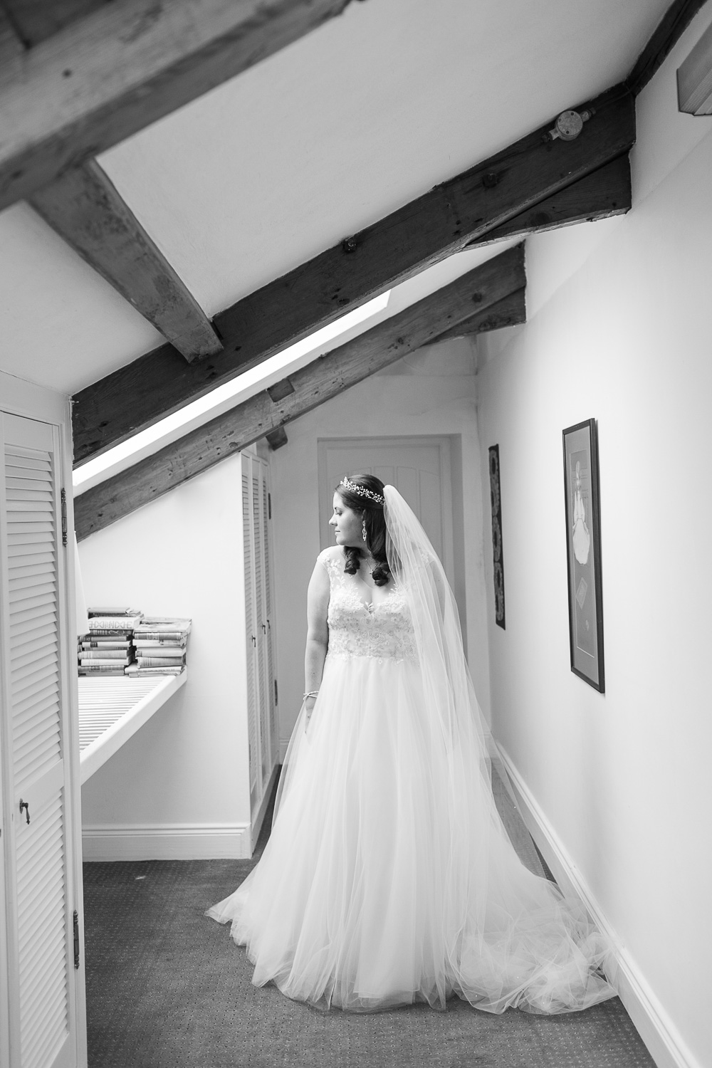Tull skirt wedding dress with a long veil and a headpiece on a bride lit by a sunroof with wooden beams
