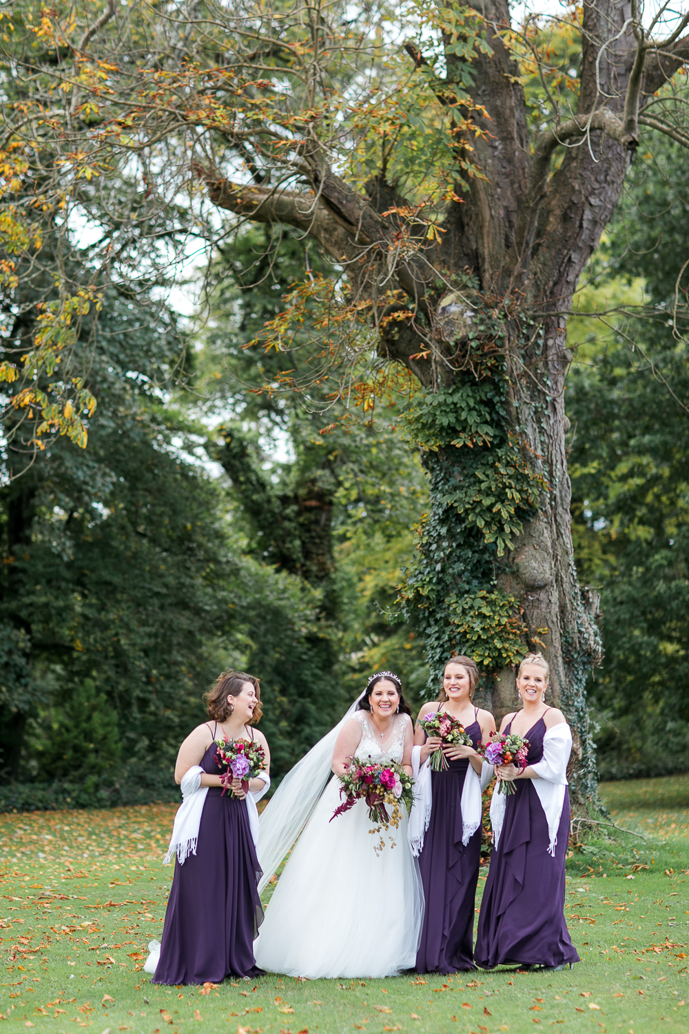purple bridesmaids dresses with the bride outside under a tree on the grass