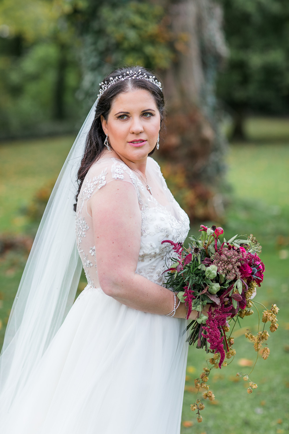Bride looking into the camera holding the flowers with her chest facing to the right