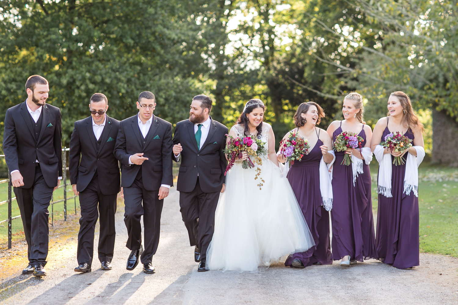 Bridal party photograph a walking smiling and laughing shot with bride and groom