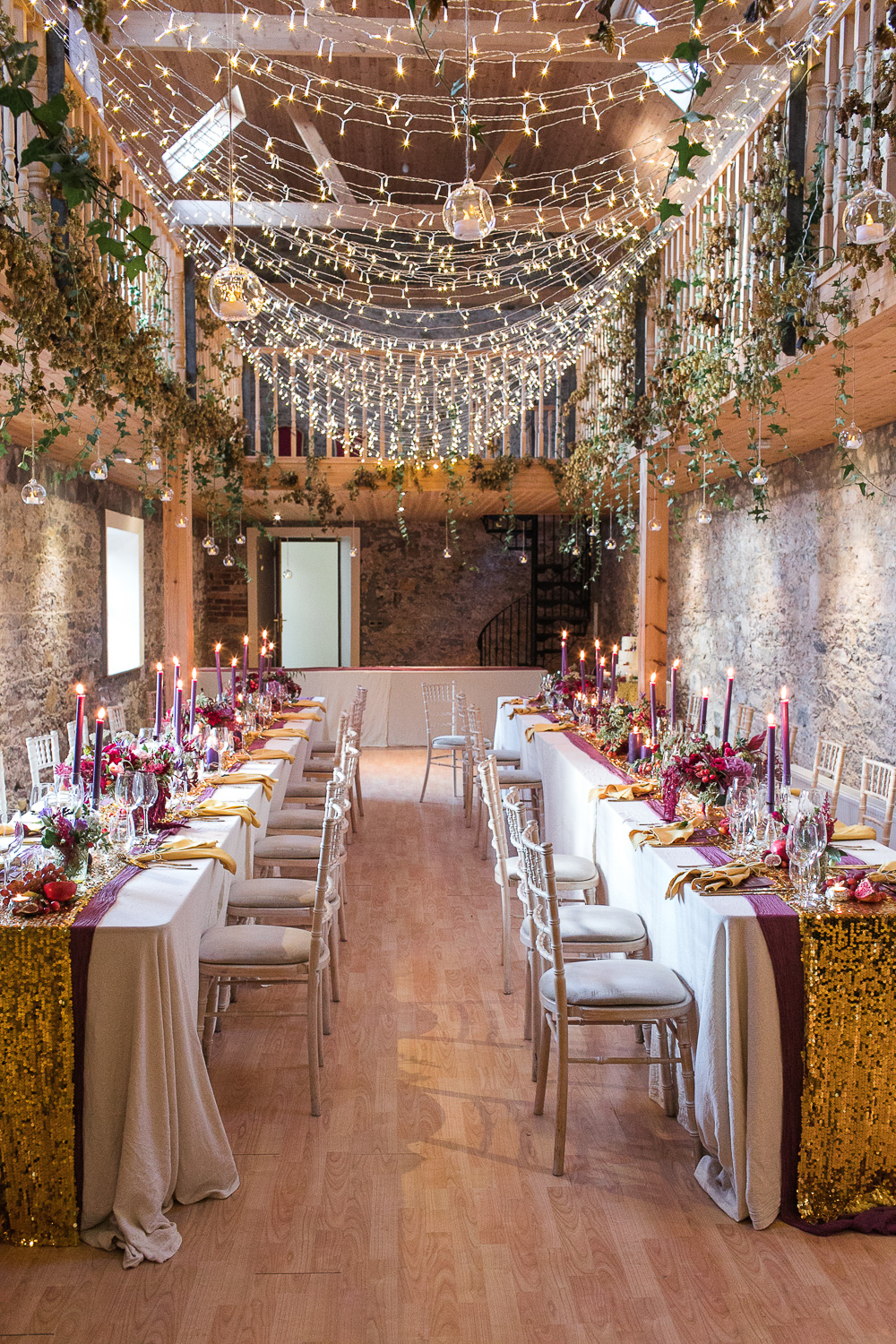 wedding function room with fairy lights sequin runners and foliage decorations