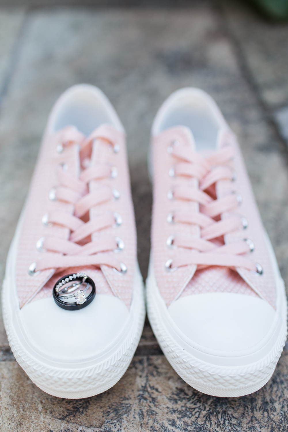 Pink Converse as wedding shoes with a bride and groom ring groom's ring is black