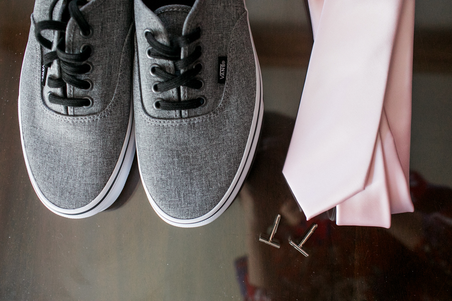 groom's grey converse with a pink tie and black cuff links