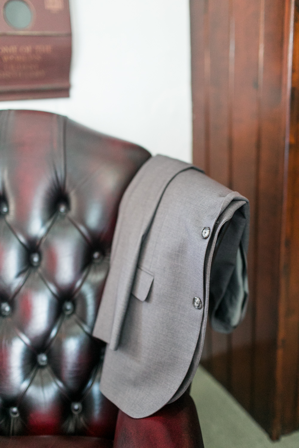 Groom's suit jacket lying on the back of a brown leather chair in bushmills hotel in northern ireland