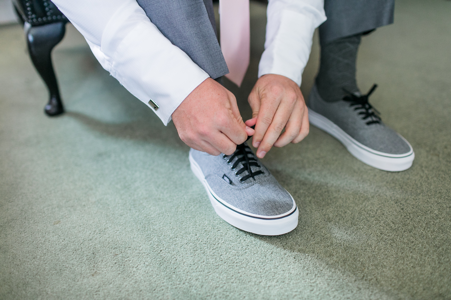 Groom putting on the grey converse before the ceremony